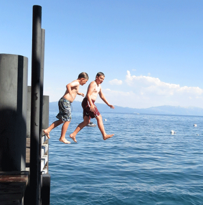 Boys jumping off a dock into a lake